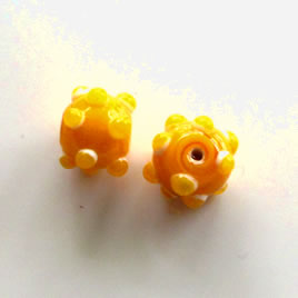 Bead, lampworked glass, yellow, 10x13mm bumpy rondelle. Pkg of 7
